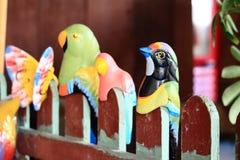 在红色篱芭的五颜六色的鸟模型 免版税库存图片