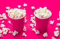在红色纸杯的玉米花在粉色背景 免版税库存图片