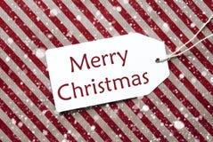 在红色纸,雪花,文本圣诞快乐的标签 库存图片