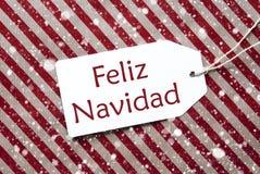 在红色纸, Feliz Navidad的标签意味圣诞快乐,雪花 免版税库存图片