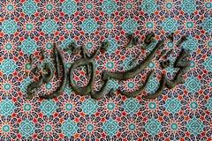 在红色纹理的清真寺装饰阿拉伯书法仿造  免版税库存图片