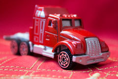 在红色纺织品背景的微型红色玩具卡车 免版税库存照片