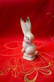 在红色纺织材料的瓷白色小兔 库存图片