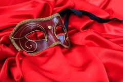 在红色缎背景的狂欢节面具 库存图片