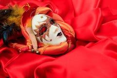 在红色缎背景的狂欢节面具 图库摄影