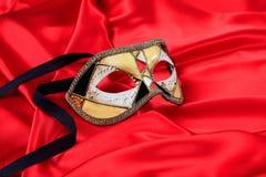 在红色缎背景的狂欢节面具 免版税图库摄影
