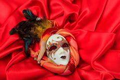 在红色缎背景的狂欢节面具 库存照片