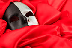 在红色缎背景隔绝的狂欢节面具 库存照片