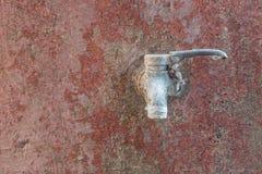 在红色老墙壁上的老生锈的水龙头 库存照片