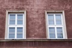 在红色老房子的门面的两个窗口 免版税库存图片