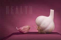 在红色背景写的健康词 大蒜作为雕塑 库存照片