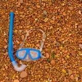 在红色背景海小卵石的水下的面具和废气管蓝色 免版税库存照片