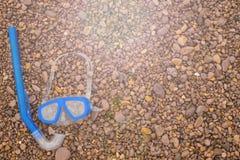 在红色背景海小卵石的水下的面具和废气管蓝色 库存图片
