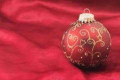 在红色背景的一个圣诞节电灯泡 免版税库存照片