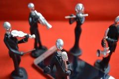在红色背景的一个手机附近戏弄有话筒和音乐家的人 库存照片