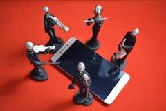 在红色背景的一个手机附近戏弄有话筒和音乐家的人 免版税库存图片