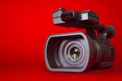 在红色背景的一台摄象机 免版税库存图片