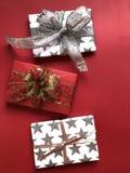 在红色背景的三豪华被包裹的圣诞礼物 免版税图库摄影