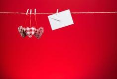 在红色背景的三长毛绒心脏 库存图片