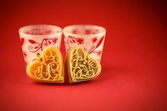 在红色背景的两个华伦泰的蜡烛 图库摄影