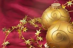 在红色背景的两个金黄圣诞节电灯泡 库存照片