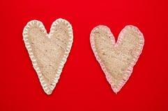 在红色背景的两自制亚麻制心脏 库存图片