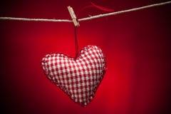 在红色背景的五颜六色的织品心脏 免版税库存图片