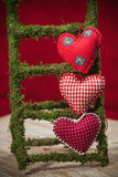 在红色背景的五颜六色的织品心脏 免版税库存照片