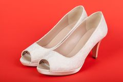 在红色背景的典雅的白色女性鞋子 图库摄影