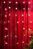 在红色背景的圣诞灯在演播室 免版税库存图片