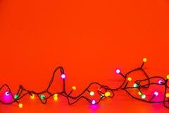 在红色背景的圣诞灯 五颜六色的边界 免版税库存图片