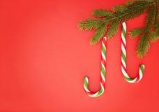 在红色背景的圣诞节构成 垂悬冷杉的两个棒棒糖分支当Xmas装饰 顶视图,平的位置 免版税库存照片