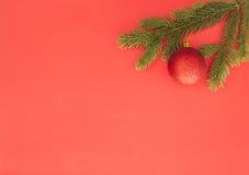 在红色背景的圣诞节构成 绿色杉树分支和Xmas装饰 顶视图,平的位置 复制空间为 库存图片