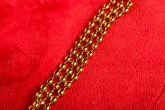 在红色背景的圣诞节金黄小珠 库存照片