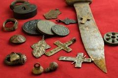 在红色背景的很多古老铜和铁对象, 18世纪的个人项目在地面发现了 免版税库存照片
