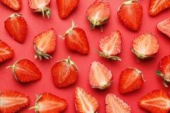 在红色背景的成熟水多的草莓 ?? 免版税库存照片