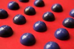 在红色背景的手工制造巧克力半球 空白的糖果 选择聚焦 免版税图库摄影