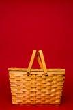 在红色背景的柳条野餐篮子 免版税库存图片