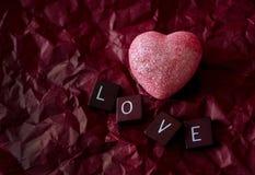 在红色背景的桃红色心脏与爱瓦片 免版税库存照片