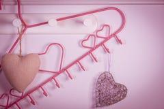 在红色背景的桃红色心脏晒衣架 背景蓝色框概念概念性日礼品重点查出珠宝信函生活纤管红色仍然被塑造的华伦泰 库存照片