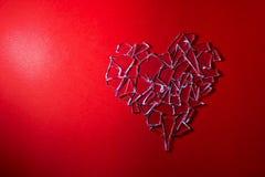 在红色背景的残破的玻璃心脏 免版税库存图片