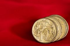 在红色背景的澳大利亚元硬币 免版税库存照片