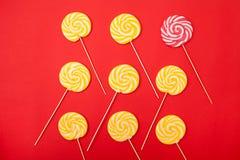 在红色背景的甜焦糖糖果 明亮的棒棒糖 免版税库存图片