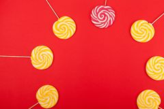 在红色背景的甜焦糖糖果 明亮的棒棒糖 库存图片