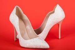在红色背景的白色女性鞋子 库存照片