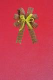 在红色背景的礼品弓 免版税图库摄影