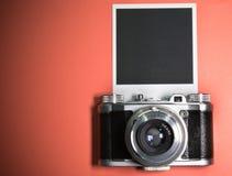 在红色背景的空白的立即照片框架突出了与老减速火箭的葡萄酒照相机和拷贝空间 免版税图库摄影