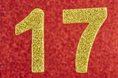 在红色背景的第十七金黄颜色 附注 免版税图库摄影