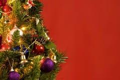 在红色背景的美丽的圣诞树 免版税图库摄影