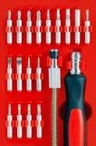 在红色背景的螺丝刀成套工具 免版税库存图片
